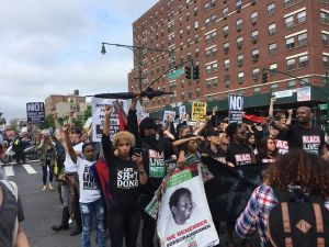 Marchers stop traffic at the intersection at 116th Street and Lenox Avenue in Harlem.