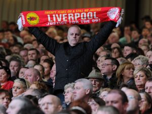 LIVERPOOL, ENGLAND - APRIL 15: (THE SUN OUT, THE SUN ON SUNDAY OUT) (NO SALES) In this handout image provided by Liverpool FC, a member of the congregation stands and holds a scarf aloft at the 24th Hillsborough Anniversary Memorial Service at Anfield on April 15, 2013 in Liverpool, England. Thousands of fans, friends and relatives took part in the service at Liverpool's Anfield Stadium to mark the 24th anniversary of the Hillsborough disaster. A total of 96 Liverpool supporters lost their lives during a crush at an FA Cup semi final against Nottingham Forest at the Hillsborough football ground in Sheffield, South Yorkshire in 1989. (Photo by )
