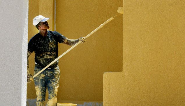A laborer paints the exterior of a new home