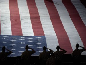 American Serviceman stand while the National Anthem is played.