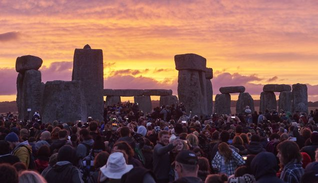 Revellers watch the sunrise as they celebrate the pagan festival of Summer Solstice at Stonehenge in Wiltshire, southern England on June 21, 2015. The festival, which dates back thousands of years, celebrates the longest day of the year when the sun is at its maximum elevation. Modern druids and people gather at the landmark Stonehenge every year to see the sun rise on the first morning of summer.