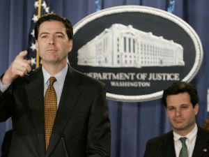 James Comey speaks with Christopher Wray during a news conference at the Justice Department on December 15, 2004.
