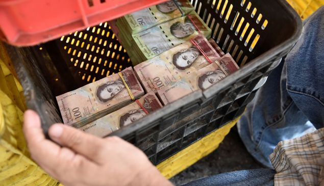CARACAS, VENEZUELA - MAY 21: A man uses a vegetables container to put a large amount of bills of the sales of days in a local market in Caracas, Venezuela on May 21, 2016. Venezuelans minimum wage is 15051.15 Bs, according to the official exchange rate its equivalent to 2389.07 US$, in contrast to the equivalence of the same amount the black market shows Venezuelans earn only 14.03 US$ per month.