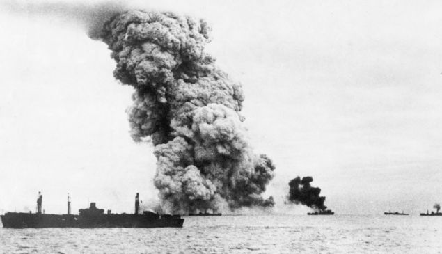 Smoke pours from an explosive carrying US ship in a naval convoy to Russia.