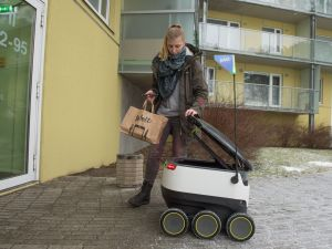 A woman receives her order delivered by one of Starship Technologies autonomous robots