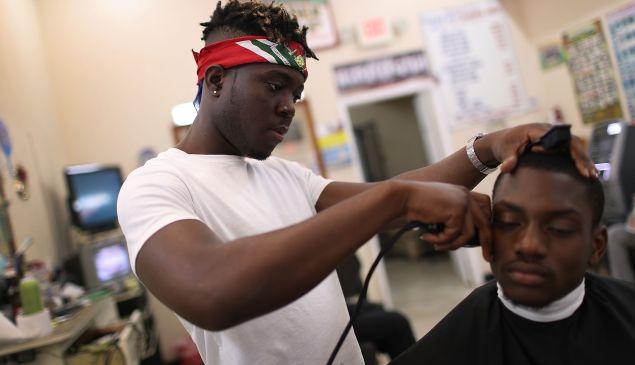 Man has his hair cut in Miami, Florida.