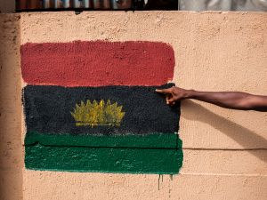 A man points at a Biafran flag painted on a wall on Old Market road in Onitsha on May 30, 2017, during a shutdown in commemoration of the 50th anniversary of the Nigerian civil war. Nigeria on May 30 marks 50 years since the declaration of an independent Republic of Biafra plunged the country into a civil war, amid renewed tensions and fresh calls for a separate state. The main pro-independence groups -- the Indigenous People of Biafra (IPOB), and the Movement for the Actualisation of the Sovereign State of Biafra (MASSOB) -- have called for a day of reflection. / AFP PHOTO / STEFAN HEUNIS