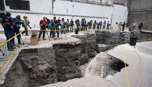 Journalists work during a tour by the archaeological site.