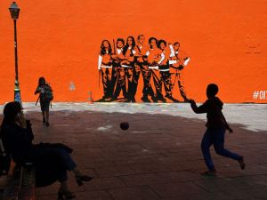"A boy plays football by a mural painting depicting the upcoming US series ""Orange Is the New Black"" to be shown on Netflix, on June 9, 2017 in Paris . / AFP PHOTO / CHRISTOPHE ARCHAMBAULT (Photo credit should read CHRISTOPHE ARCHAMBAULT/AFP/Getty Images)"