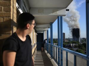 """A resident of a nearby council estate watches smoke billowing from Grenfell Tower on June 14, 2017 in west London. The massive fire ripped through the 27-storey apartment block in west London in the early hours of Wednesday, trapping residents inside as 200 firefighters battled the blaze. Police and fire services attempted to evacuate the concrete block and said """"a number of people are being treated for a range of injuries"""", including at least two for smoke inhalation. / AFP PHOTO / DANIEL LEAL-OLIVAS"""