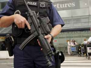 An armed British police officer patrols outside of Heathrow Airport in London, England.