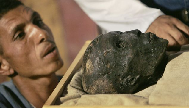 An archaeological worker looks at the face of the linen-wrapped mummy of King Tutankhamun as he is removed from his stone sarcophagus in his underground tomb in the famed Valley of the Kings in Luxor, 04 November 2007. It was the first time that the true face of ancient Egypt's boy king Tutankhamun was revealed to the public since he died in mysterious circumstances more than 3,000 years ago.