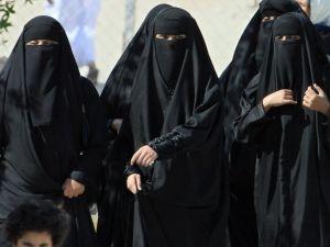 Saudi women cross a street in Saudi Arabia.