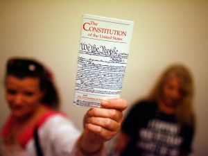 A teacher holds up a copy of the U.S. Constitution.