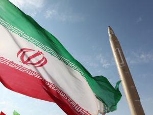 An Iranian flag flutters next to a missile.