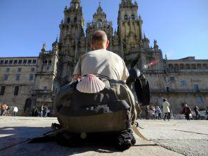 A Camino de Santaigo pilgrim rests and looks at the Santiago de Compostela Cathedral.