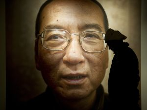 A man walks in front of a poster of Chinese dissident and peace prize laureate Liu Xiaobo.