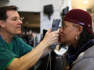 Mary Sanders (R) has her eyes examined by a Remote Area Medical (RAM) volunteer optometrist John Weis during a free clinic held at the Oakland-Alameda County Coliseum.