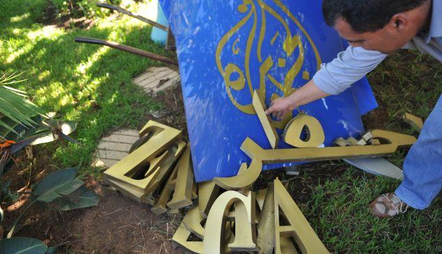 Staff members dismantle the signs of the TV station Al-Jazeera in Rabat on November 4, 2010.