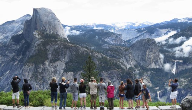 Visitors look out from Glacier Point in Yosemite National Park, California.