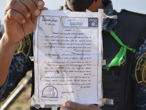 A member of Iraqi security forces holds a flyer released by the Islamic State (IS) religious police ordering local residents to close all commercial shops during the daily prayer times otherwise face punishment according to the Islamic Sharia law.