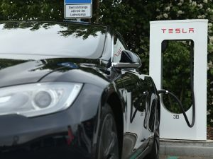 A Tesla electric-powered sedan stands at a Tesla charging station.