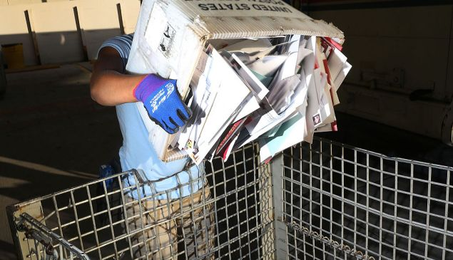 MIAMI, FL - DECEMBER 14: Shantel Hill, a City Carrier Assistant to the United States Postal Service, works to unload her mail truck at the Processing and Distribution Center after collecting mail on the busiest mailing day of the year for the U.S. Postal Service on December 14, 2015 in Miami, Florida. With 10 days to go until Christmas eve, today the postal service was expecting 612 million pieces of mail to be sent, from first class letters to priority packages. (Photo by Joe Raedle/Getty Images)