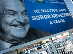 """A poster with US billionaire George Soros is pictured on July 6, 2017 in Szekesfehervar, Hungary. The head of Hungary's largest Jewish organisation says a """"poisonous"""" poster campaign by the government that targets US billionaire George Soros is stoking anti-Semitic sentiments and urged its immediate scrapping. / AFP PHOTO / ATTILA KISBENEDEK / TO GO WITH AFP STORY"""