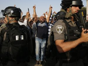 A Palestinian Muslim raises his arms and shouts slogans before Israeli security forces in the Haram al-Sharif compound, in the complex in the old city of Jerusalem on July 27, 2017, as clashes erupted at the sensitive holy site after thousands of Muslim worshippers entered to end a boycott of the compound over new Israeli security measures.