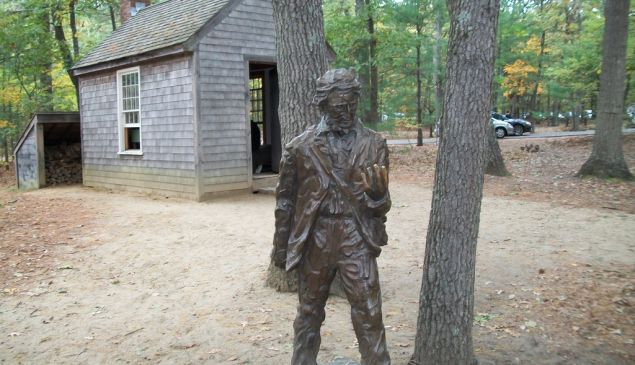 A statue of Henry David Thoreau in front of a replica of his cabin in Concord, Massachusetts.