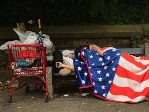A homeless man sleeps under an American Flag blanket on a park bench in the Brooklyn borough of New York City.