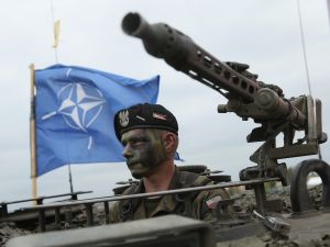 A soldier of the Polish Army sits in a tank as a NATO flag flies behind.