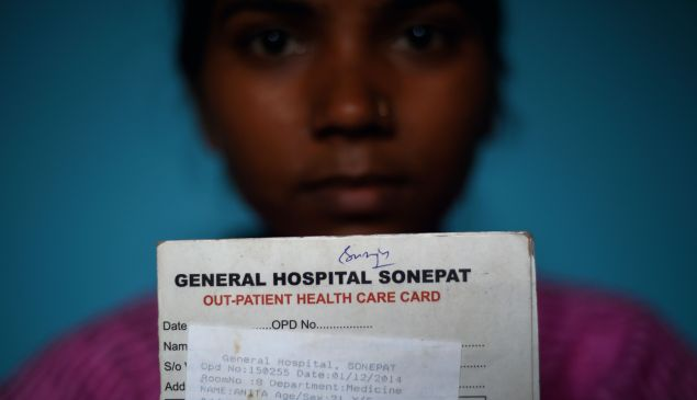 Indian tuberculosis (TB) patient Anita, 23, holds a medical card from a government hospital as she sits at her home in Sonipat.