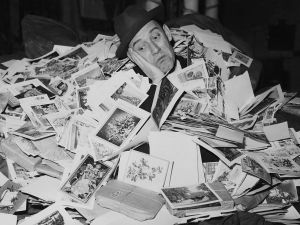 Portrait of English comedian Tommy Trinder nearly buried under a huge pile of Christmas cards, just some of the million cards sent to the Adelphi Hotel in an appeal for old cards to be sent to hospitals, London, January 9th 1957. (Photo by Evening Standard/Fox Photos/Getty Images)