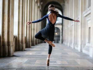 PARIS, FRANCE - JANUARY 08: Amanda Derhy, ballerina and ballet dancer, is wearing a Mariia Dancewear blue leotard, an Adidancewear black skirt, and Repetto dance shoes, and is performing ballet dance moves, at the Louvre, on January 8, 2017 in Paris, France.