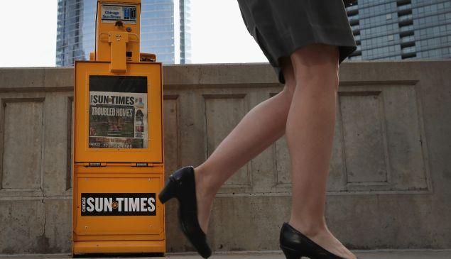 A pedestrian walks past a Chicago Sun-Times newspaper box.