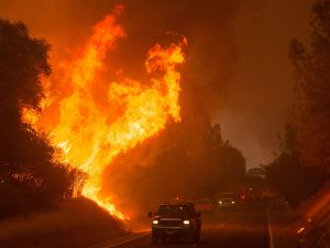 """Motorists drive past flames from the """"Wall Fire"""" along Forbestown Road in Oroville, California on July 8, 2017."""