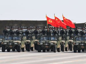 Chinese soldiers carry the flags of the Communist Party, the state, and the People's Liberation Army during a military parade at the Zhurihe training base in China's northern Inner Mongolia region on July 30, 2017.