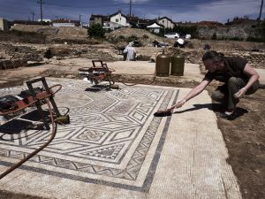 An archaeologist works on a mosaic on July 31, 2017, on the archaeological antiquity site of Sainte-Colombe, near Vienne, eastern France.