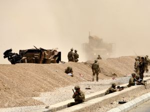 U.S. soldiers keep watch near the wreckage of their vehicle at the site of a Taliban suicide attack in Kandahar on August 2, 2017.