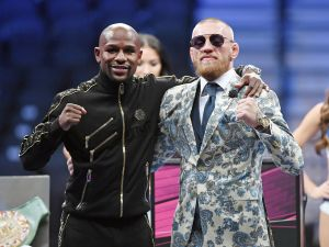 Floyd Mayweather Jr. and Conor McGregor pose for pictures during a news conference after Mayweather's 10th-round TKO victory in their super welterweight boxing match on August 26, 2017.