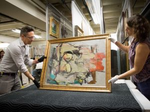 The recovered painting by Willem de Kooning is readied for examination by UA Museum of Art staff Nathan Saxton (r), Exhibitions Specialist, and Kristen Schmidt, Registrar.