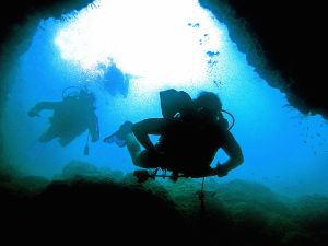 Divers at the entrance of an underwater cave.