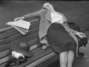 A woman sits asleep on a bench.
