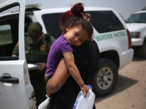 A mother and child, 3, from El Salvador await transport to a processing center for undocumented immigrants after they crossed the Rio Grande into the United States.