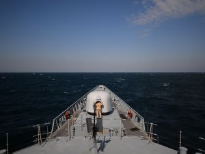 "A navy man inspects a cannon of the Romanian frigate ""Regina Maria"" during a military drill on the Black Sea."