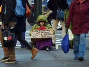 A homeless woman sits on 5th Avenue at 42nd Street in New York City.