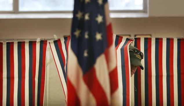 A voter emerges from a voting booth.