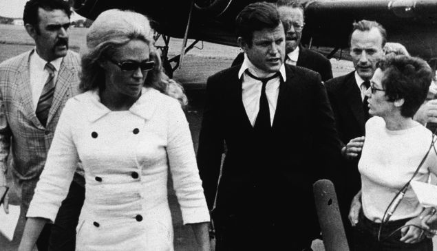 Reporters question American Senator Edward Kennedy (center, with neck brace) and his wife Joan Kennedy (left, in white coat and dark glasses) as they walk across the tarmac after returning from the funeral of Mary Jo Kopechne, Hyannis, Massachusetts, July 22, 1969. Kopechne died when a car driven by Kennedy went over the side of a bridge on Chappaquiddick Island four days earlier. (Photo by Hulton Archive/Getty Images)