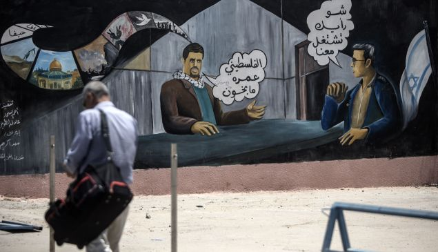 """A man walks past a mural painting with Arabic writing warning people not to work as agents for the Israeli intelligence on the Palestinian side of he Israeli border terminal of Erez in the Gaza strip on July 13, 2016. Arabic writing in a cartoon format on the wall painiting reads: """"How about working for us,""""(R) an Israeli agent asks a Palestinian man (C) who replies: """"Palestinians will never be traitors."""" / AFP / MAHMUD HAMS"""